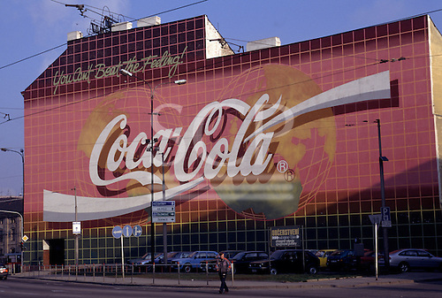 "Prague, Czech Republic. Massive ""Coca - Cola"" advertisement on a wall; signs in Czech under; cars parked."