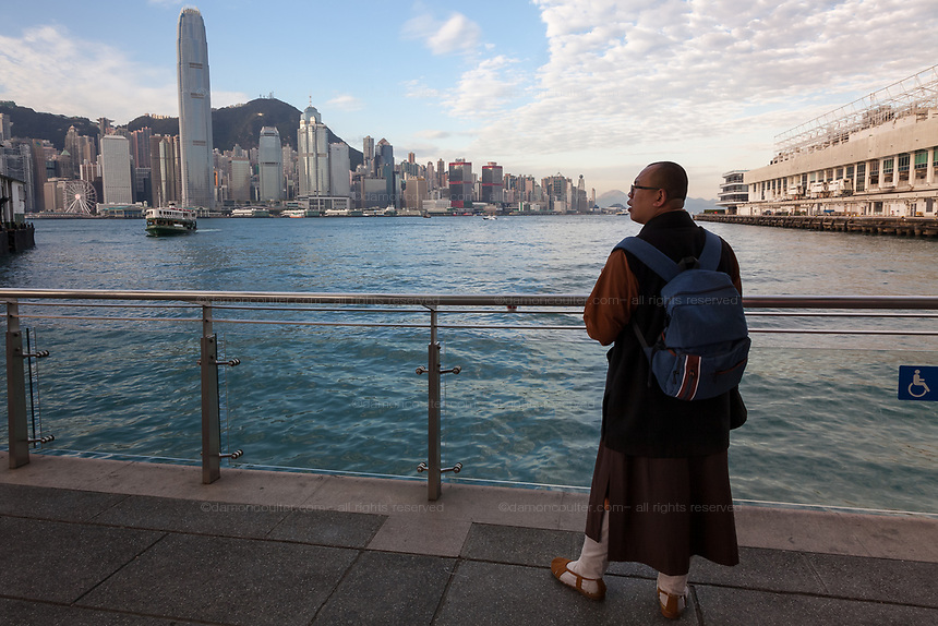A monk takes in the view of Hong Kong Bay as he waits for the Star Ferry at the pier in Tsim Sha Tsui with the skyscraper of the International Finance Centre behind.  Hong Kong, China. Thursday January 11th 2018