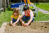 MR / Schenectady, NY. Girl (4) and her brother (6) plant in family garden in raised bed in back yard. MR: Jan2, Jan3. ID: SPR. © Ellen B. Senisi