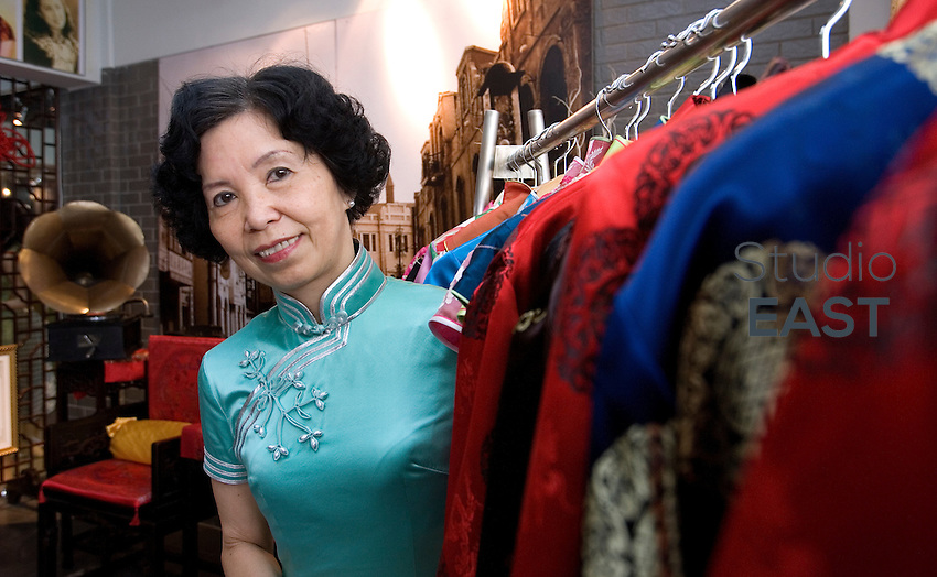 Wang Weiyu poses in a Qipao traditional dress and behind other Qipaos, in her Qipao salon, in Shanghai, China, on April 19, 2010. Photo by Lucas Schifres/Pictobank . Inspired by Wong Kar-Wai's film 'In mood for love', Wang Weiyu, a 62-year-old former Japanese teacher, opened her 'Qipao salon' in 2007. It became famous when a TV show mentioned it. Now about 370 Shanghaiese ladies, mostly senior, come regularly to her Salon to learn how to dance, walk, and sit, wearing the Qipao. This elegant dress, originally worn by Manchus, became the symbol of Shanghai 'Pearl of the Orient', in the thirties. But during the seventies, the Cultural Revolution saw it as decadent and bourgeois, and forbade it. 50-year-old women who couldn't wear it when they were young now come back to the cultural and traditional Qipao. 'When  I wear it, I feel pretty, I am always in a good mood' comments a 47-year-old woman.