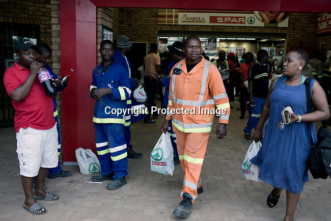 Workers shop in a grocery store in Maropong township outside Lephalale, South Africa. Many people have moved in from rural areas and Zimbabwe to find work at the new Medupi coal power plant. The plant, operated by the state company Eskom will be the fourth largest in the world and is expected to produce electricity in early 2015. Many people live in bad conditions in Maropong, trying to make a living and compete about the few jobs available.