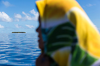 A Tuvaluan woman looks out from a boat as it passes through the Funafuti atoll, Tuvalu. March, 2019.