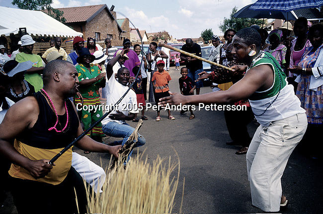 SOWETO, SOUTH AFRICA MARCH 12: Unidentified men tease each other during a traditional wedding ceremony on March 12, 2005 in Soweto, Johannesburg, South Africa. The families came together to meet each other families before a western styled wedding was held.  Soweto is South Africa&rsquo;s largest township and it was founded about one hundred years to make housing available for black people south west of downtown Johannesburg. The estimated population is between 2-3 million. Many key events during the Apartheid struggle unfolded here, and the most known is the student uprisings in June 1976, where thousands of students took to the streets to protest after being forced to study the Afrikaans language at school. Soweto today is a mix of old housing and newly constructed townhouses. A new hungry black middle-class is growing steadily. Most residents work in Johannesburg but the last years many shopping malls has been built, and people are starting to spend their money in Soweto.  <br /> (Photo by Per-Anders Pettersson)