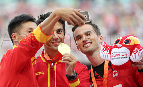 22.08,2015. Beijing, China.   Second placed Wang Zhen of China (L-R) takes a photo of winner Miguel Angel Lopez of Spain and third placed Benjamin Thorne of Canada during the medal ceremony for the Men's 20 km Race Walk during the 15th International Association of Athletics Federations (IAAF) Athletics World Championships in Beijing, China, 23 August 2015.