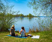 Deutschland, Bayern, Chiemgau, bei Uebersee-Feldwies: diese zwei jungen Frauen geniessen die ersten warmen Sonnenstrahlen bei einem kleinen Picknick am Chiemsee | Germany, Bavaria, Chiemgau, near Uebersee-Feldwies: two young women enjoying spring sunshine at lake Chiemsee
