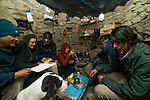 Andean Mountain Cat (Leopardus jacobita) conservationist, Michael Clifford, veterinarian, Deana Clifford, biologist, Cintia Tellaeche, conservationist, Eliana Segura, biologist, Juan Reppucci, and conservationist, Jorge Luiz, cramming into field kitchen with Domestic Dog (Canis familiaris), Abra Granada, Andes, northwestern Argentina