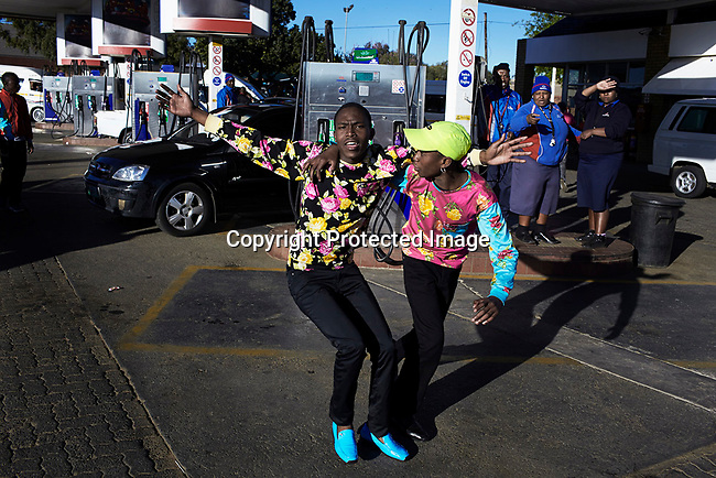 SOWETO, SOUTH AFRICA SEPTEMBER 29: Izikhothane youth display their clothes at a petrol station on September 29, 2012 in Dobsonville, Soweto, South Africa. Hundreds of the Izikhothane kids later gathered in Thokoza Park and moved on to other areas in Soweto, to show off their dance moves and play loud music. The Izikhothane bling kids are the new fears of residents and parents in the townships of Johannesburg. They buy (and sometimes burn and destroy) fancy brand clothes and shoes in Soweto. They also like to drink and display expensive bottles of alcohol. Many of these kids are desperate to get the latest clothes and the pressure is hard on their parents. (Photo by: Per-Anders Pettersson)