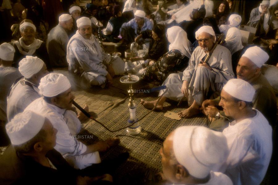Egypt. Tanta. 1996. During the three days of festival (mouled) for Sidi Ahmad el-Badaoui, greatest Muslim saint of the country, pilgrims came with their families and get together on mats and carpets and eat, smoke hooka around Tanta's mosque. .Egypte. Tanta. 1996. Pendant les trois jours de fete (mouled) en l'honneur de Sidi Ahmad el-Badaoui, plus grand saint musulman du pays, des pelerins venus en famille, s'installent autour de la mosquee de Tanta sur des nattes et sur des tapis, et entre autres mangent, fument le narghile.