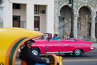Havana, Cuba - An American car and a Coco Taxi on the Malecón road facing Havana Bay. Classic American cars from the 1950s, imported before the U.S. embargo, are commonly used as taxis in Havana.
