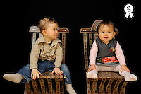 Two baby twins on chairs  (Licence this image exclusively with Getty: http://www.gettyimages.com/detail/85071282 )