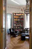 Towering metal bookcase and parquet flooring in a room dedicated to reading and family activities, lit by a tin chandelier