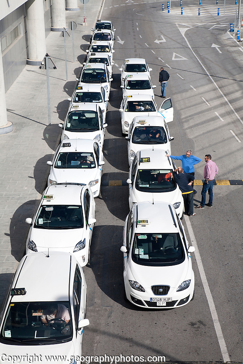 Line of white taxis queueing outside Malaga airport, Spain