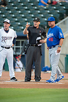 Home plate umpire Brian Walsh talks to Northwest Arkansas Naturals manager Darryl Kennedy (8) (left) and Tulsa Drillers manager Scott Hennessey (46) on May 13, 2019, at Arvest Ballpark in Springdale, Arkansas. (Jason Ivester/Four Seam Images)