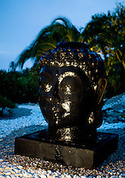 A Buddha in the garden shines in the glow of an outdoor light
