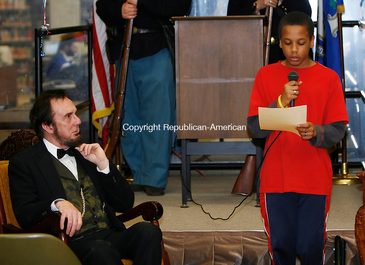WATERBURY, CT, 02/11/08- 021109BZ10- Lewis Dube, impersonating Abraham Lincoln, looks on as Alex Gatling reads one of Lincoln's letters during a performance in honor of the 16th President's Bicentennial at the Silas Bronson Library in Waterbury Wednesday night. <br /> Jamison C. Bazinet Republican-American