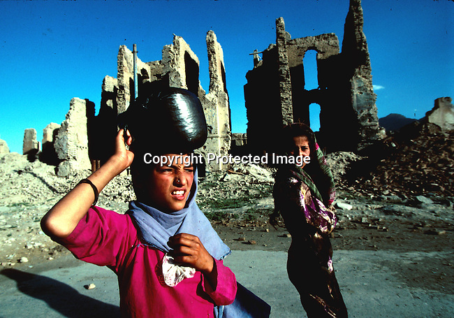 Girls looking for water in central Kabul, Afghanistan. The Taliban took over most of Afghanistan in 1996, and have forced the people to live under strict muslim law. Girls are not allowed to attend schools and women are not allowed to work. .©Per-Anders Pettersson/iAfrika Photos