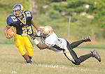 The Gazette Laurel running back #23 DeAntae Love escapes the grasps of Oxon Hill's #55 Daniel Simmons during the first-half of Laurel's 21-20 victory over Oxon Hill on Friday afternoon in Laurel.Laurel vs Oxon Hill Football