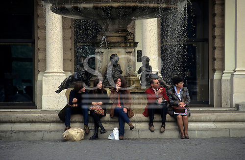 Slovakia. People sitting on steps leading up to a fountain.