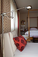 A steel angle-poise floor lamp stands beside a leather chaise longue in a bedroom with a four poster bed and red and white furnishings.