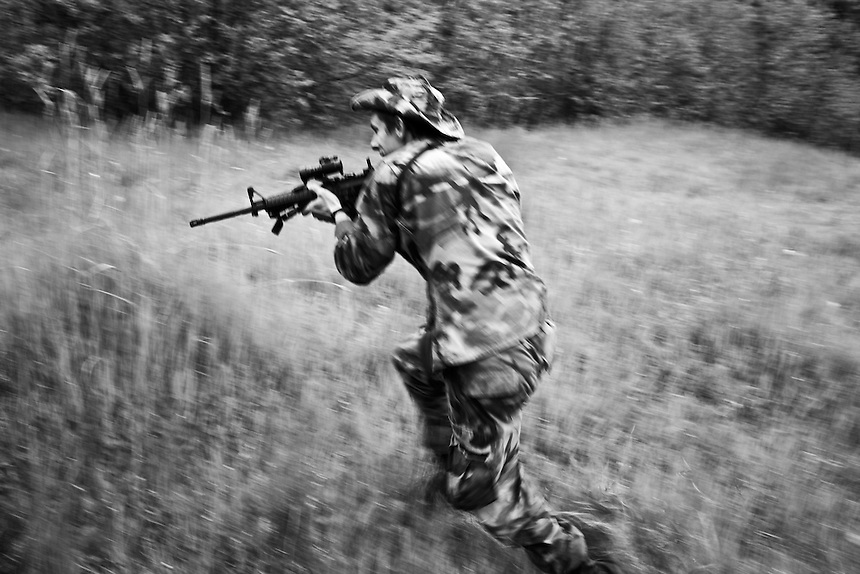 Cody Hoyt runs towards a mock enemy during a combat training exercise at a Conservation Corps. camp near Priest Lake, Idaho.