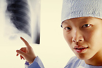 Female Asian Doctor in surgical scrubs, points at a chest X-ray. portrait, medicine, occupations, medical.