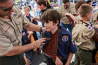 NWA Democrat-Gazette/CHARLIE KAIJO Den leader Steve Chapman helps Lucas Hurd, 9, of Bentonville make an arm sling from neckerchief during the First Friday event, Friday, July 6, 2018 at the Downtown Square in Bentonville. <br />
