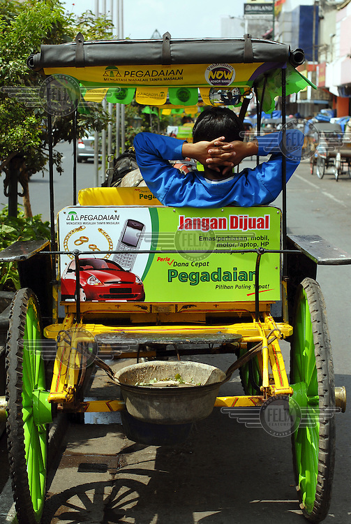 A driver of a horse carriage waits for customers on Jalan Malioboro, the main commercial street in central Yogyakart. His carriage displays an advert for Perum Pegadaian a state-owned pawn shop company.