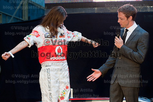 Fashion model Reka Ebergenyi (L) presents McLaren Formula One driver Jenson Button (R) of Britain the new  traditional Hungarian overall desgin by Istvan Kalmar (not pictured) during the annual Hugo Boss party just prior to the Hungarian F1 Grand Prix in Budapest, Hungary. Thursday, 28. July 2011. ATTILA VOLGYI