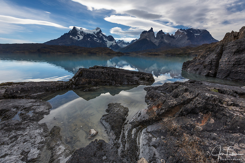 Wide-angle view of the Paine Massif - Cerro Paine Grande, the Cuernos del Paine and Monte Almirante Nieto - with rocks and Lake Pehoe in the foreground.  Torres del Paine National Park in Patagonia, Chile.  A UNESCO World Biosphere Reserve. The peaks and clouds are reflected on the lake surface.