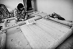 A woman weaves a carpet on a loom in her home in Mazar-e Sharif 28 September 2013. (John D McHugh)
