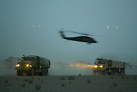 A US Army UH-60 BLACKHAWK helicopter fllies past the convoy of trucks moving north in Iraq. The convoy travelled into the night to make their way into areas of Iraq that have been cleared by the initial strike.