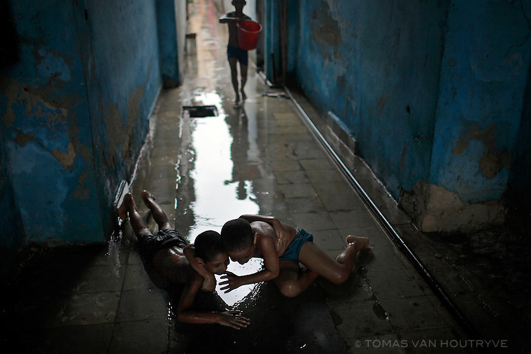 Boys play in puddles in a slippery hallway on a rainy day in Havana, Cuba on 26 October 2008.
