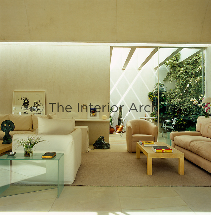 The spacious living room has a curved high ceiling and glass doors leading to a covered courtyard garden