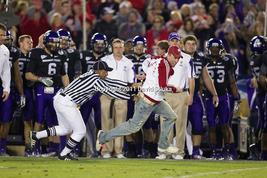 A referee chases a Wisconsin Badgers fan who ran onto the field during the 2011 Rose Bowl NCAA Football game against the TCU Horned Frogs in Pasadena, California on January 1, 2011. TCU won 21-19. (Photo by David Stluka)