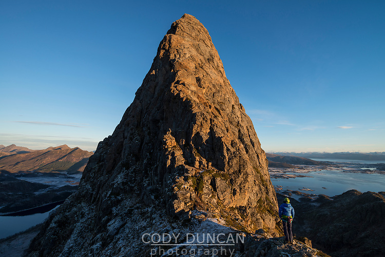 Female climber looks at route to summit of Reka mountain peak, Vesterålen, Norway