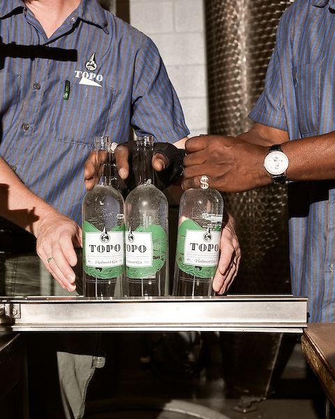 June 18, 2013. Chapel Hill, North Carolina<br />  Head distiller George Dusek, left, and Simon Hinson fill and cork bottles of TOPO Gin.<br />  TOPO, Top of the Hill Distillery, the brainchild of owner Scott Maitland and Spirit Guide Esteban McMahan, is located in the old N&O Building on Franklin Street. Making gin, vodka and American whiskey from locally sourced wheat, they are one of the few distilleries bringing  organic liquor to ABC shelves around the state.