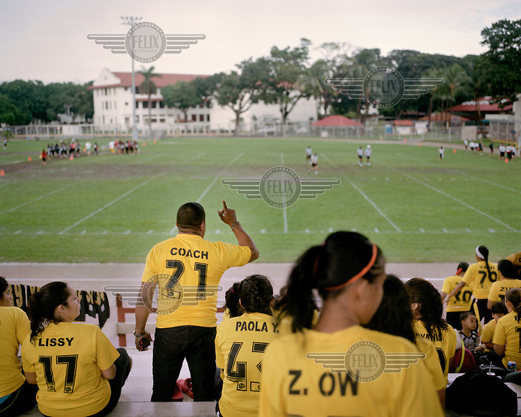The coach of the Golden Eagles female team gesticulates during a match of Flag Football (a non-tackling version of American Football) against the Black Eagles at the Balboa Municipal Stadium which is administered by the Panama Canal Authority. <br /> <br /> The Panama Canal Zone is an area extending 8kms out, in each direction, from the waterway's central line, was a territory controlled by the United States between 1903 and 1979. After a 20 year period of joint administration, the Canal came under the full control of Panama in 1999. The Canal opened to shipping in 1914 and during its tenure was of great strategic importance to the US, enabling it to rapidly move its naval fleet between the Atlantic and Pacific Oceans. However, its economic value came not directly from shipping fees but from the stimulus to trade that the waterway created. One hundred years after it opened in 2014 it is due to have its locks upgraded to cater for the super sized container ships of the 21st Century.  <br /> During the era of American administration thousands of US citizens populated the Canal Zone, living and working under US law in towns built to American standards. Not all of these people returned north after the canal came under full Panamanian control many stayed on, their identities tied to the region.