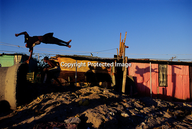 Boys play on a concrete pipe on August 12, 2001 in Site B Khayelitsha, a township about 35 kilometers outside Cape Town, South Africa. Khayelitsha is one of the poorest and fastest growing townships in South Africa. People usually come from the rural areas in Eastern Cape province to find work as maids and laborers. Most people don't find work and the unemployment rate is very high, together with lot of violence and a growing HIV-Aids epidemic it's a harsh area to live in. (Photo by: Per-Anders Pettersson).