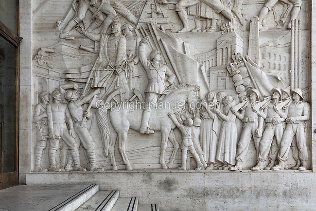 Relief of Benito Mussolini, 1939, by Publio Morbiducci, at the entrance of the Palazzo degli Uffici, headquarters of EUR SpA, built 1937-39 in Fascist style, designed by Gaetano Minnucci, 1896-1980, and built as part of the EUR or Expositione Universale di Roma (Rome Universal Exhibition), planned by Marcello Piacentini, Rome, Italy. The exhibition was to take place in 1942 to celebrate the 20th anniversary of the fascist regime. Fascist architecture developed in the late 1920s and 1930s, as a modernist style in times of nationalism and totalitarianism under Benito Mussolini. It is characterised by large, square, symmetrical buildings with little or no decoration, often inspired by ancient Rome and designed to convey strength and power. Picture by Manuel Cohen