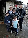 "THIS PHOTO IS AVAILABLE AS A PRINT OR FOR PERSONAL USE. CLICK ON ""ADD TO CART"" TO SEE PRICING OPTIONS.   Giltena Duda and her husband Ismet Sabanaj, here with three of their six children, live in the Zemun Polje Roma neighborhood of Belgrade, Serbia. Ms. Duda is pregnant with her seventh child. They are Roma refugees from Kosovo, and thus legally marginalized in Serbia. They built their home on unregistered land and pirate their electrical hookup. Without legal residency, their children can't attend a regular school, and they have difficulties getting formal employment. Yet both participate in an adult literacy program sponsored by the Branko Pesic School, where their children attend classes. The school is supported by Church World Service."