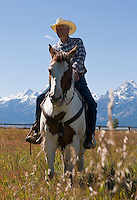 Cowboy on horse with snowy Teton Range in the distance