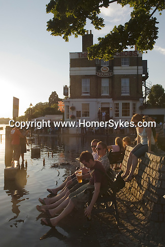 Flooding The White Cross Pub. Richmond Upon Thames, Surrey, England  Weekend visitors enjoy a drink at high tide.