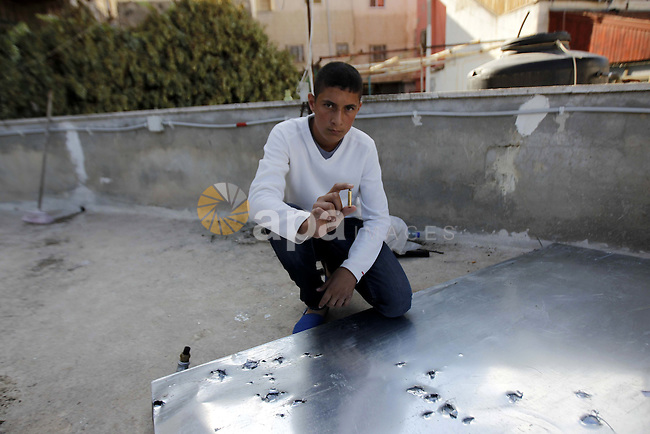 A Palestinian youth displays a bullet at the scene where Moataz Higazi was killed by Israeli security forces on the roof of his house in the mostly Arab east Jerusalem neighbourhood of Abu Tor on October 30, 2014. Hijazi was the suspected of an assassination attempt on a hardline campaigner for Jewish prayer rights at Jerusalem's flashpoint Al-Aqsa mosque compound. The attack sent tensions in the city soaring to a new high, following months of almost daily clashes between Palestinians and Israeli police in Jerusalem's occupied eastern sector. Photo by Muammar Awad