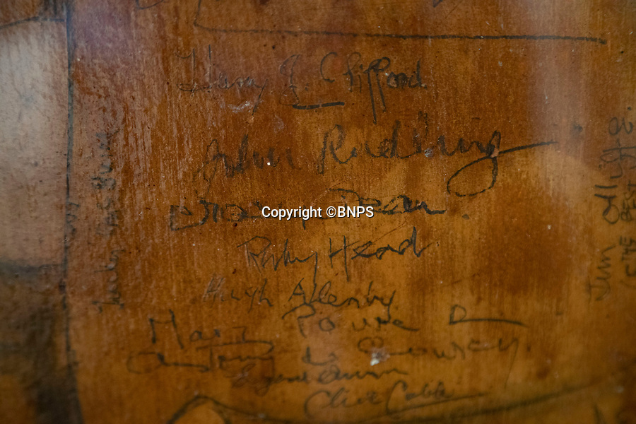 BNPS.co.uk (01202 558833)<br /> Pic: CorinMesser/BNPS<br /> <br /> Signatures on one of the pieces of ceiling the couple have saved. <br /> <br /> Sections of a torn-down pub ceiling which are covered in 250 signatures from World War Two heroes have been salvaged and turned into a memorial.<br /> <br /> The merry airmen left their mark during raucous evenings at the George and Dragon in the village of Clyst St George in Devon.<br /> <br /> Many of the brave men who signed or drew on the wood ceiling perished in the war in the skies with the Luftwaffe.<br /> <br /> One of them, Sergeant Albert Stilin, of 257 Squadron, was killed aged 21 when he crashed his Hurricane into this pub's roof on September 30, 1942. Another airman later put the initials 'RIP' put after his name.<br /> <br /> The ceiling was taken down in 1975 and half of it was destroyed. <br /> <br /> Robin and Suzannah Holwell recovered the surviving planks from a RAFA association store room in 2009 and have carried out a decade-long preservation project, putting the sections in frames and researching the men behind signatures.