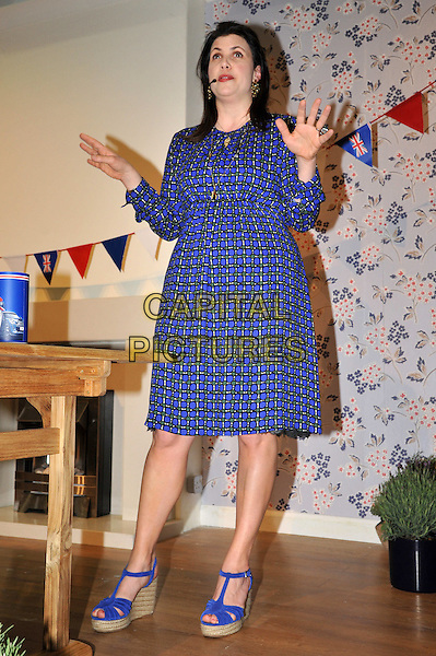 Kirstie Allsopp workshop at the B&Q How to Theatre, Ideal Home Show, Earls Court Exhibition Centre, London, UK. The property guru hosts workshop to encourage visitors to be more creative when styling their home. She shares ideas for the Diamond Jubilee and demonstrates how to make bunting..March 28th, 2012.full length dress blue print  hands arms  .CAP/BF.©Bob Fidgeon/Capital Pictures.
