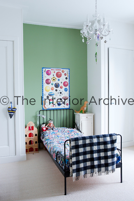 A boy's bedroom is painted in 'Breakfast Room Green' by Farrow & Ball. A vintage football poster hangs on the wall above the bed, which is dressed with bed linen printed with coloured footballs by 'Molo'