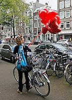 Amsterdam- Vrouw loopt met fiets en hartvormige ballonnen op de Rozengracht