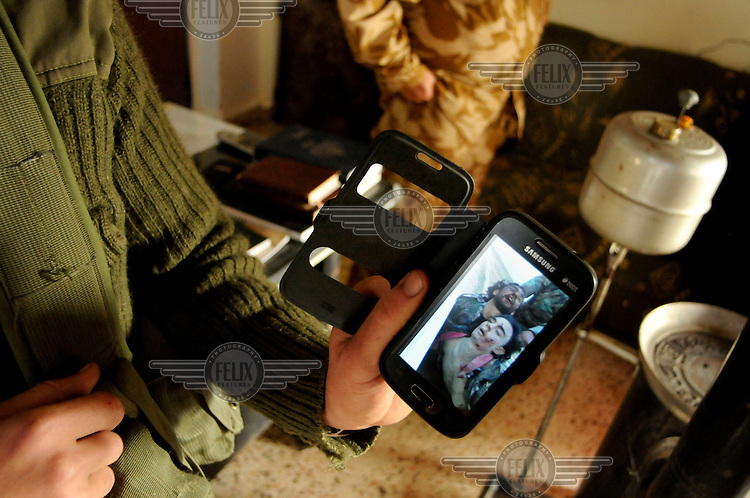 At an army base soldiers show footage, on a smartphone, of enemy (ISIS) fighters, presumably killed in combat by government troops.