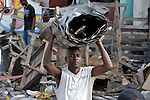 A man carries scavenged roofing material through the devastated center of Port-au-Prince, Haiti, which was ravaged by a January 12 earthquake.