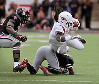 STAFF PHOTO BEN GOFF  @NWABenGoff -- 09/13/14 Texas Tech defender Tevin Madison trips up Arkansas running back Alex Collins in the first quarter of the game in Jones AT&T Stadium in Lubbock, Texas on Saturday September 13, 2014.